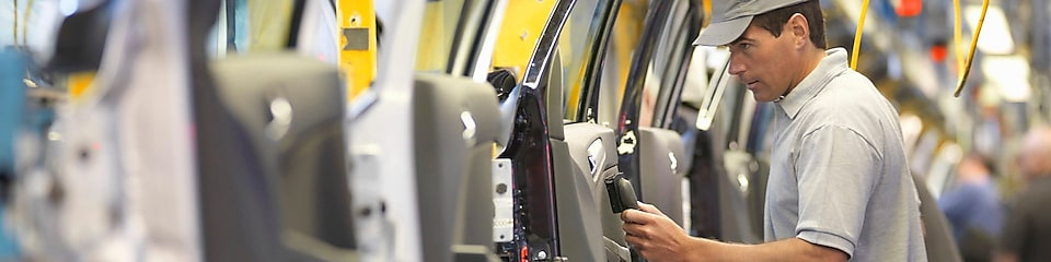 man holding wire looking at machine