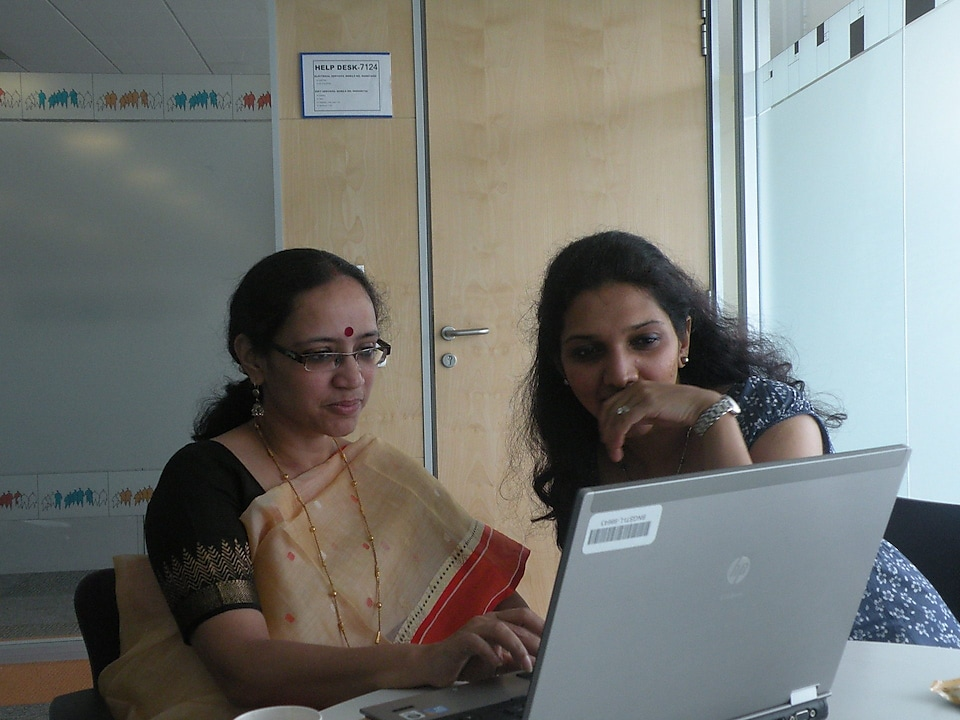 Poonam and colleague chatting in front of the laptop