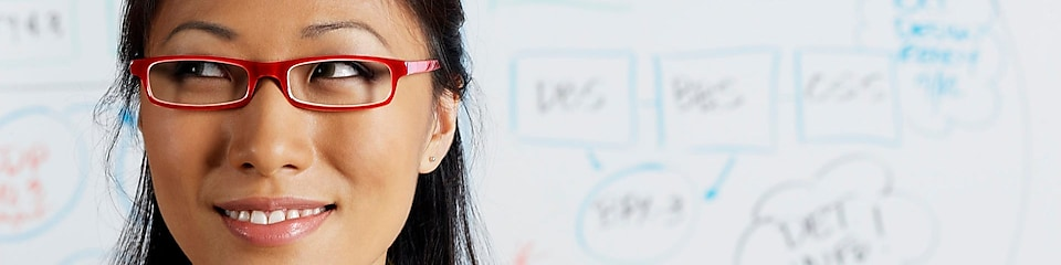 Close up of Asian businesswoman smiling in front of whiteboard