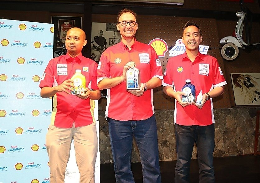 people posing with shell lubricant product can