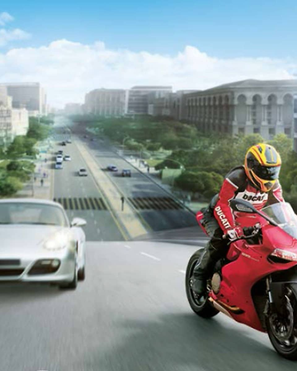 Red motorcycle and rider on a road with cars and buildings in the background