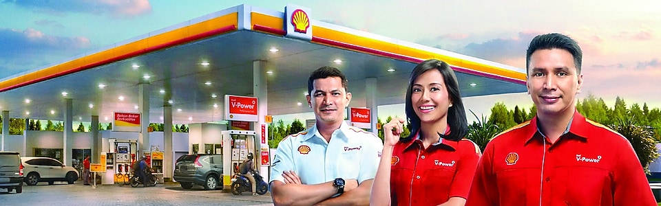 People posing in front of Shell station